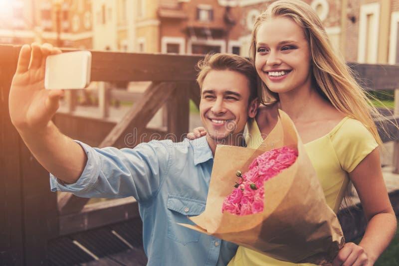 Pares jovenes románticos que hacen Selfie usando el teléfono fotos de archivo