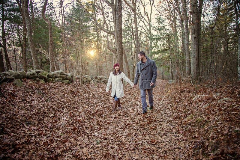 Pares jovenes románticos que llevan a cabo las manos que caminan en el bosque fotografía de archivo