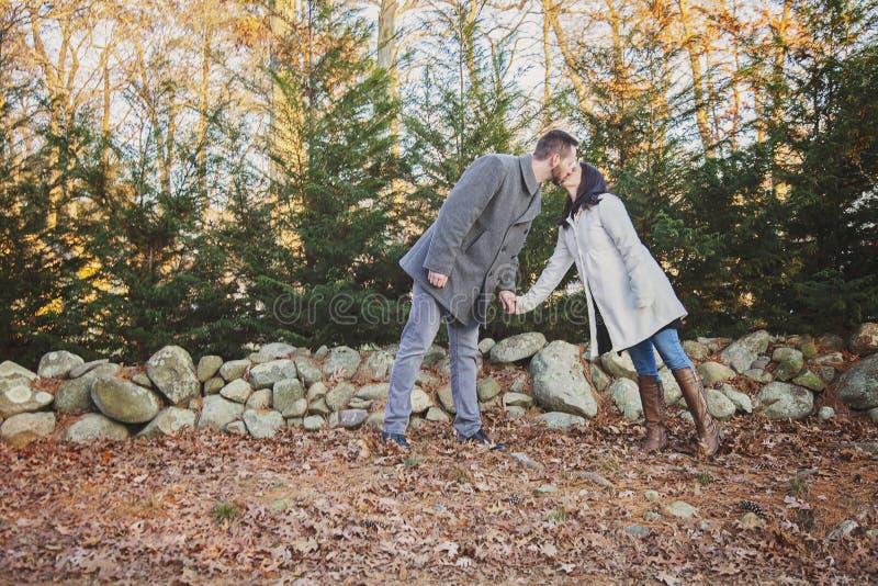 Pares jovenes románticos que se besan por una pared de la roca foto de archivo libre de regalías