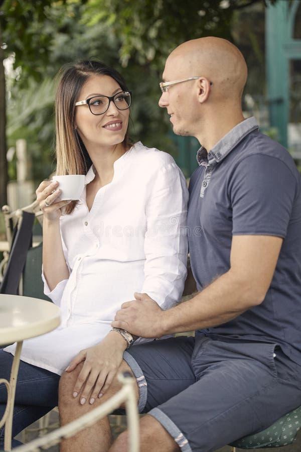 Pares jovenes, sentándose en café junto, llevando a cabo las manos fotografía de archivo libre de regalías
