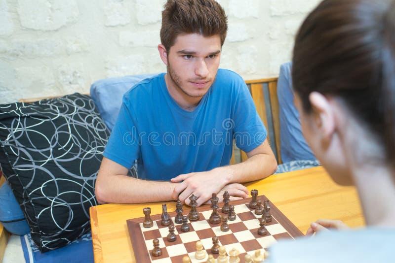 Pares jovenes serios que juegan a ajedrez fotografía de archivo