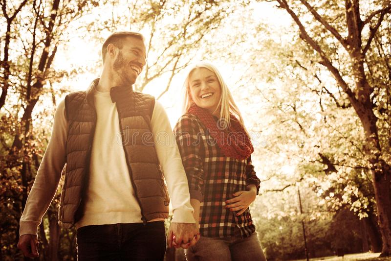 Pares jovenes sonrientes en el parque que lleva a cabo las manos y hablar foto de archivo