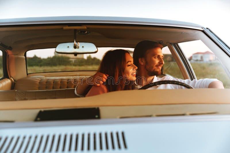 Pares jovenes sonrientes que abrazan mientras que se sienta junto dentro de un coche imagenes de archivo