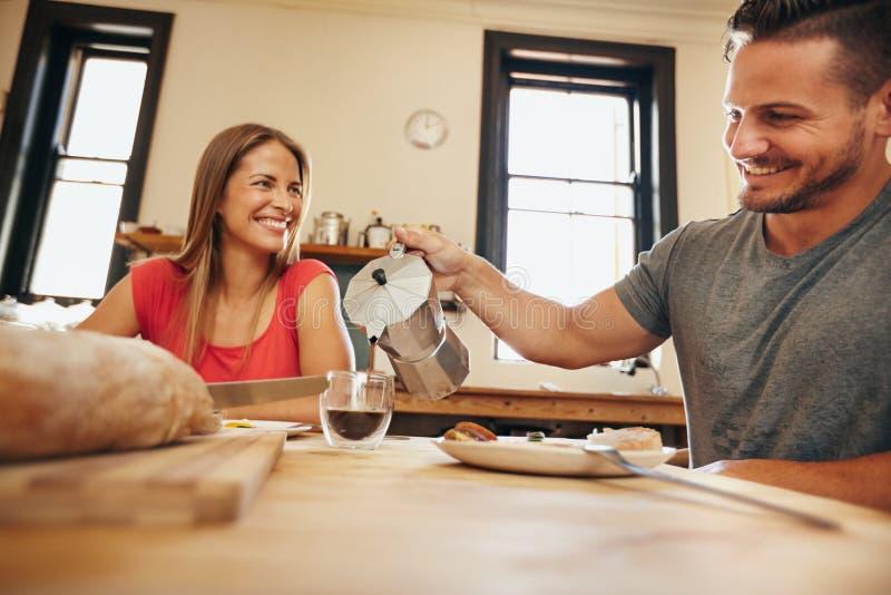 Pares jovenes sonrientes que desayunan junto en cocina fotos de archivo