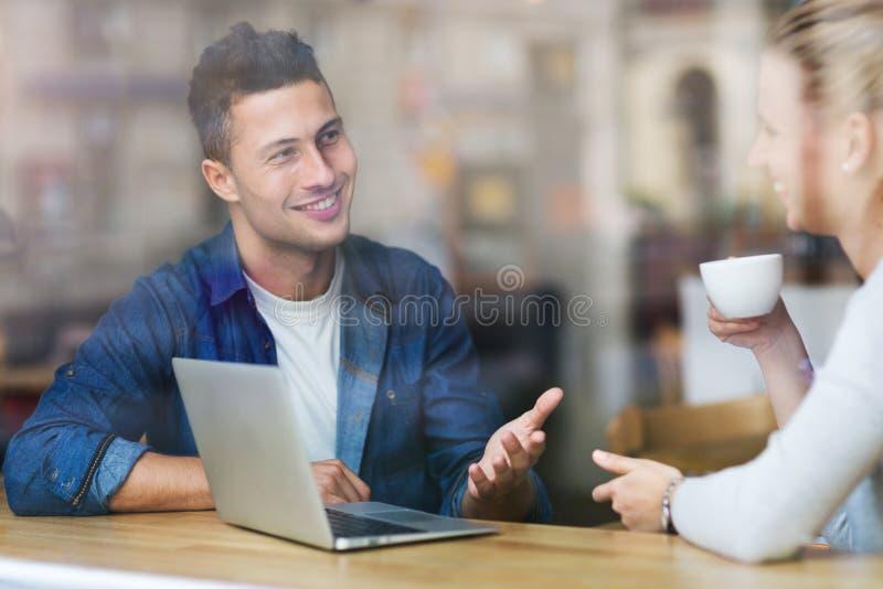 Pares jovenes usando el ordenador portátil en el café foto de archivo