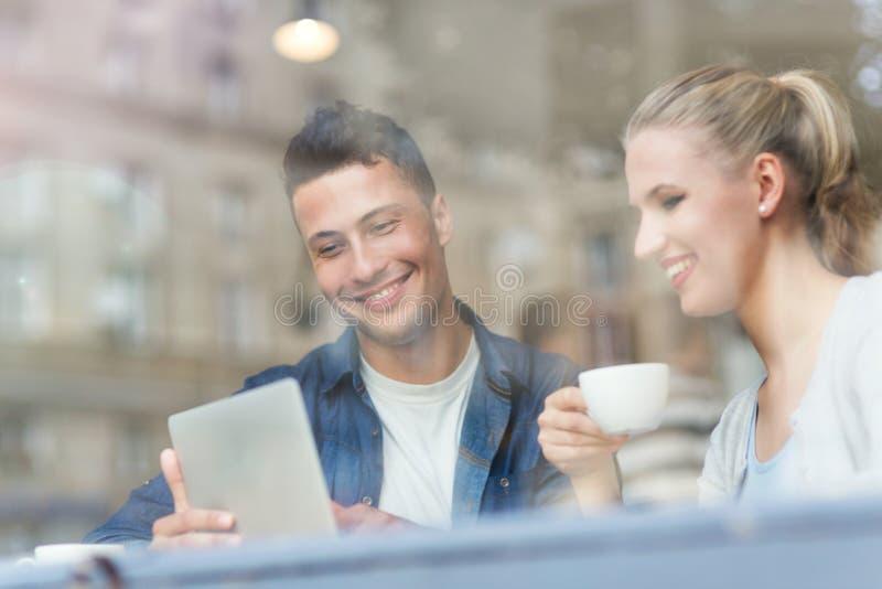 Pares jovenes usando el ordenador portátil en el café foto de archivo libre de regalías
