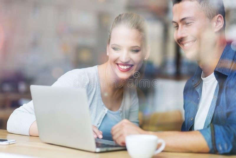 Pares jovenes usando el ordenador portátil en el café imagen de archivo