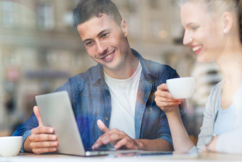 Pares jovenes usando el ordenador portátil en el café imagen de archivo libre de regalías