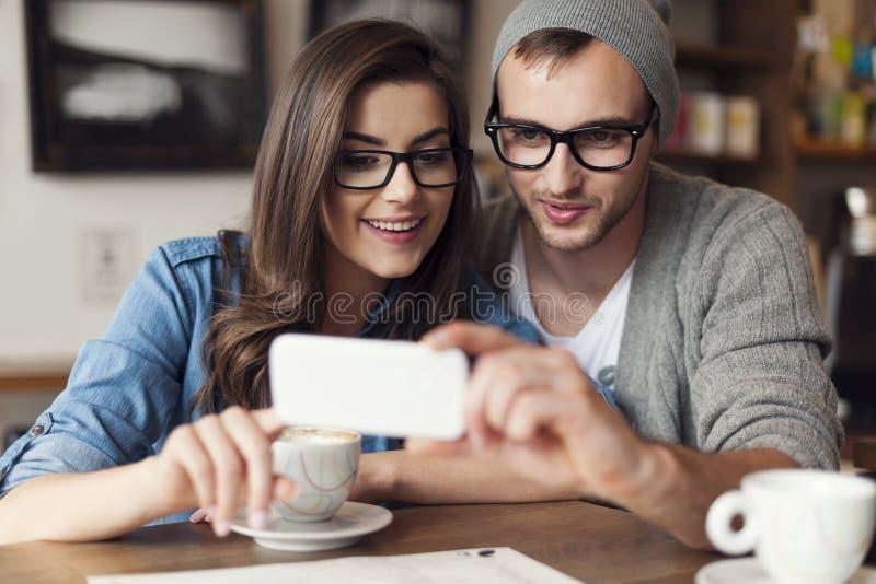 Pares jovenes usando el teléfono móvil fotografía de archivo libre de regalías