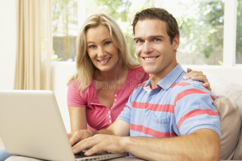 Pares jovenes usando la computadora portátil en el país foto de archivo libre de regalías