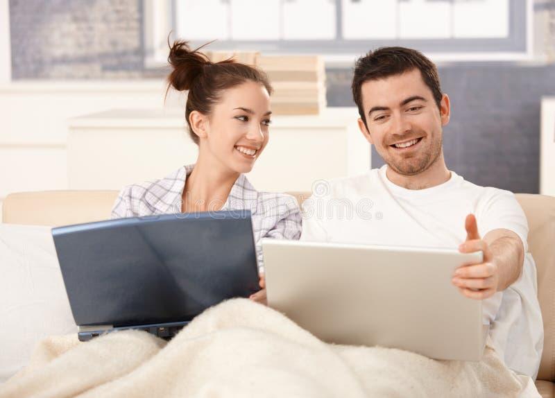 Pares jovenes usando la computadora portátil en la cama en el país que sonríe imagenes de archivo