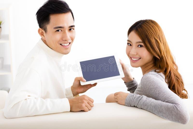 Pares jovenes usando la tableta en el sofá imagen de archivo
