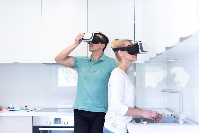 Pares jovenes usando los vidrios de las VR-auriculares de realidad virtual foto de archivo libre de regalías