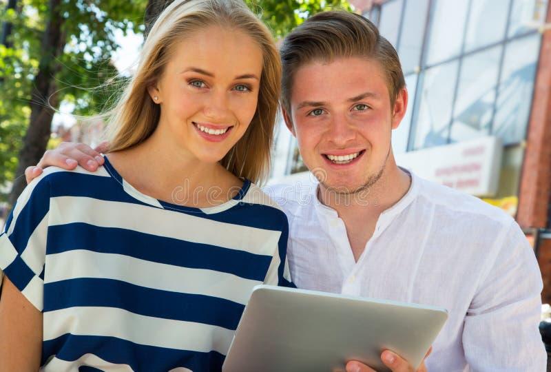Pares jovenes usando una tableta digital imágenes de archivo libres de regalías