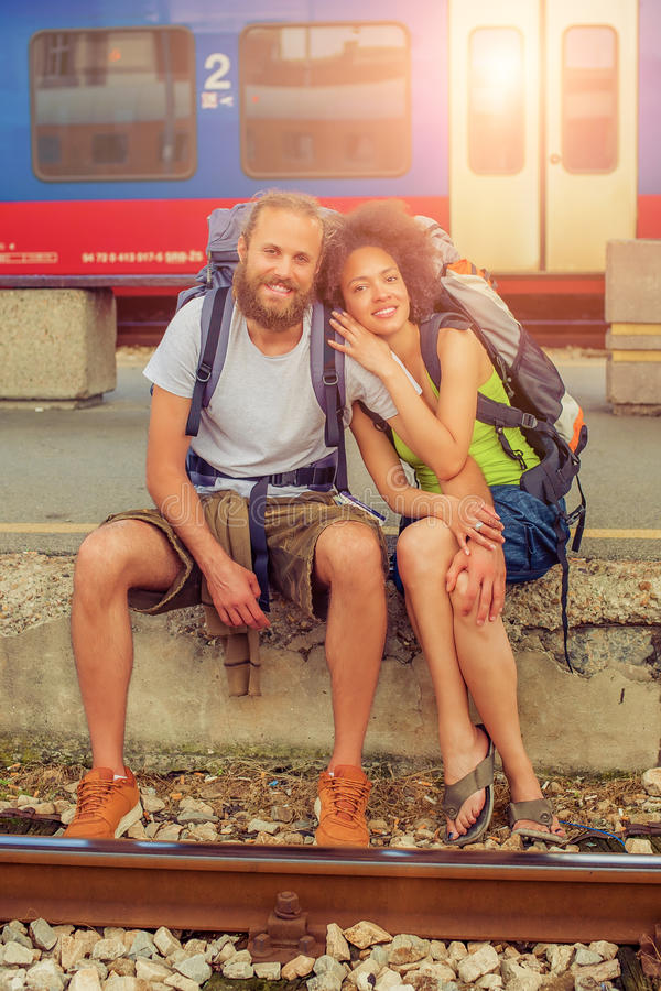 Pares jovenes y hermosos felices de los turistas que se sientan en el carril fotografía de archivo libre de regalías