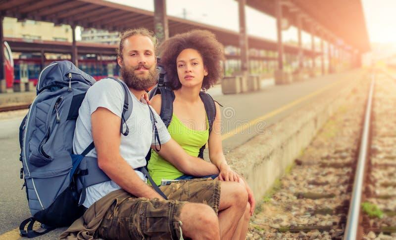 Pares jovenes y hermosos felices de los turistas que se sientan en el carril fotos de archivo libres de regalías