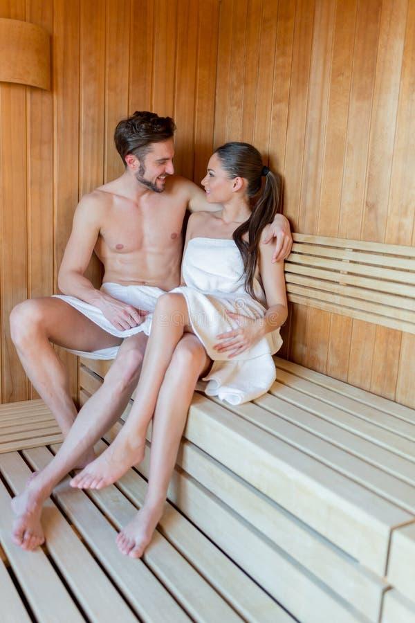 Pares jovenes y hermosos que se relajan y que abrazan en una sauna con fotografía de archivo