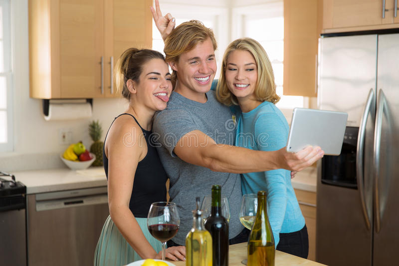 Pares jovenes y tercera rueda que tienen actitud de la diversión en casa para una imagen del selfie a la parte en su red social foto de archivo libre de regalías