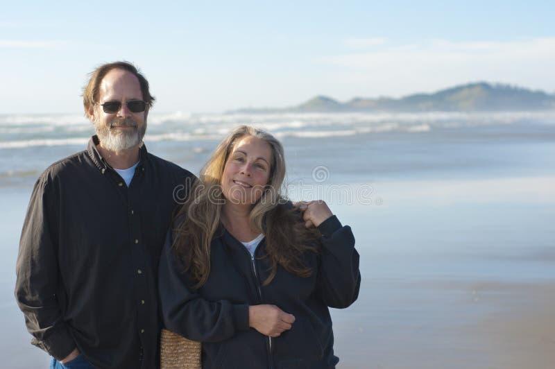 Pares jubilados en la playa imágenes de archivo libres de regalías