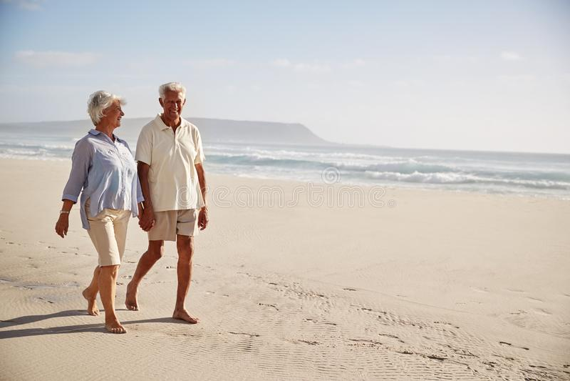 Pares jubilados mayor que caminan a lo largo de la playa de común acuerdo junto fotos de archivo libres de regalías