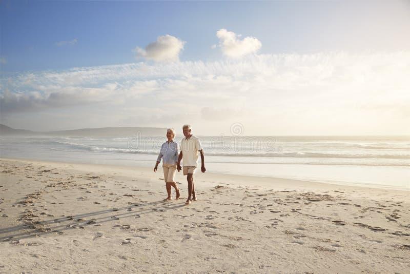 Pares jubilados mayor que caminan a lo largo de la playa de común acuerdo junto imagen de archivo libre de regalías