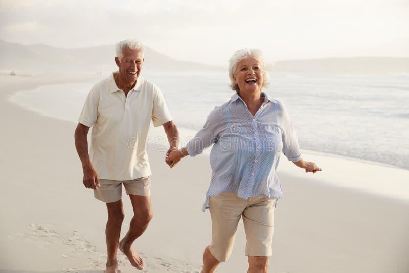 Pares jubilados mayor que corren a lo largo de la playa de común acuerdo junto imagenes de archivo