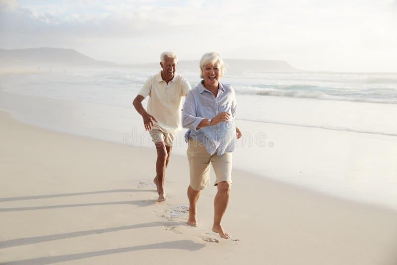 Pares jubilados mayor que corren a lo largo de la playa del verano junto foto de archivo