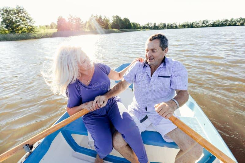Pares jubilados que pasan tiempo en un barco imagen de archivo