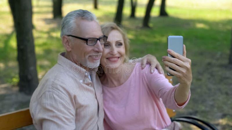 Pares jubilados que toman la foto del selfie por el smartphone en parque, memorias de las vacaciones foto de archivo