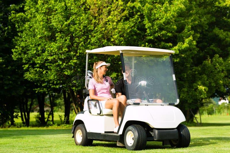 Pares juguetones jovenes con el carro de golf en un curso imagenes de archivo