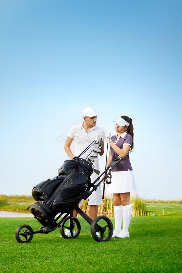 Pares juguetones jovenes que juegan a golf en campo de golf foto de archivo