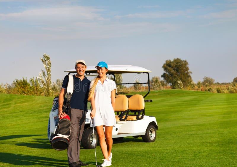 Pares juguetones jovenes que juegan a golf en un campo de golf imágenes de archivo libres de regalías