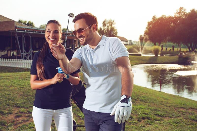 Pares juguetones jovenes que juegan a golf en un campo de golf foto de archivo libre de regalías