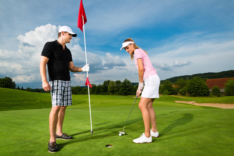 Pares juguetones jovenes que juegan a golf en un curso fotografía de archivo