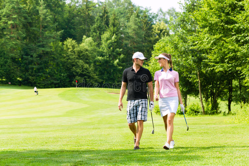 Pares juguetones jovenes que juegan a golf en un curso fotos de archivo