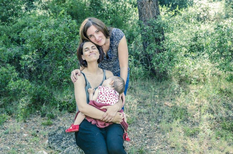 Pares lésbicas adoráveis com seu bebê na natureza fotos de stock