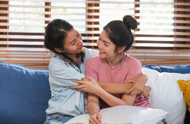 Pares lésbicas asiáticos felizes para abraçar-se em casa com amor no sofá na sala de visitas, conceito do estilo de vida de LGBTQ foto de stock