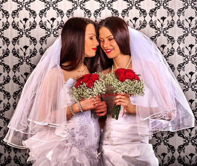 Pares lésbicas no beijo nupcial do vestido do casamento foto de stock