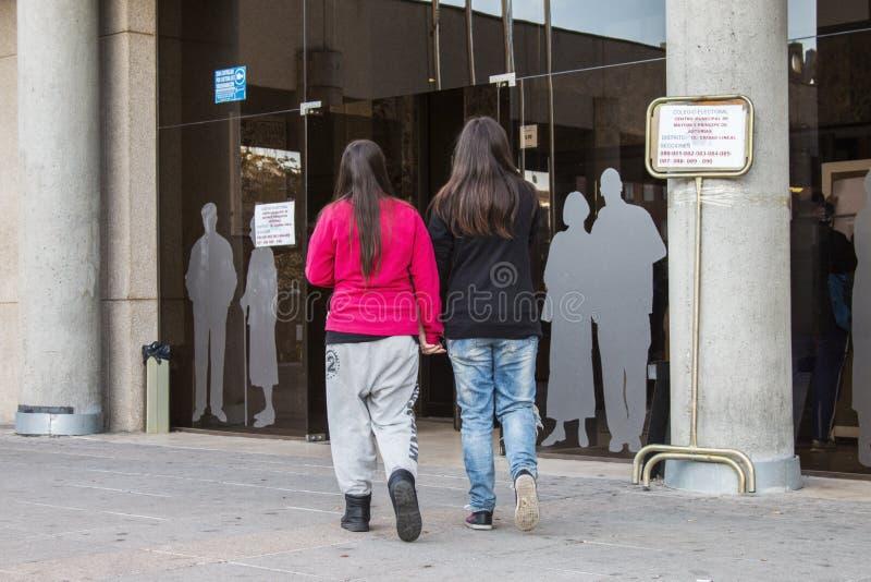 Pares lésbicas novos que andam junto para o colégio eleitoral no dia de eleição geral espanhol no Madri, Espanha foto de stock