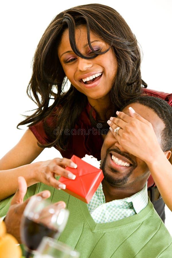 Pares: La mujer sorprende al hombre con el regalo foto de archivo