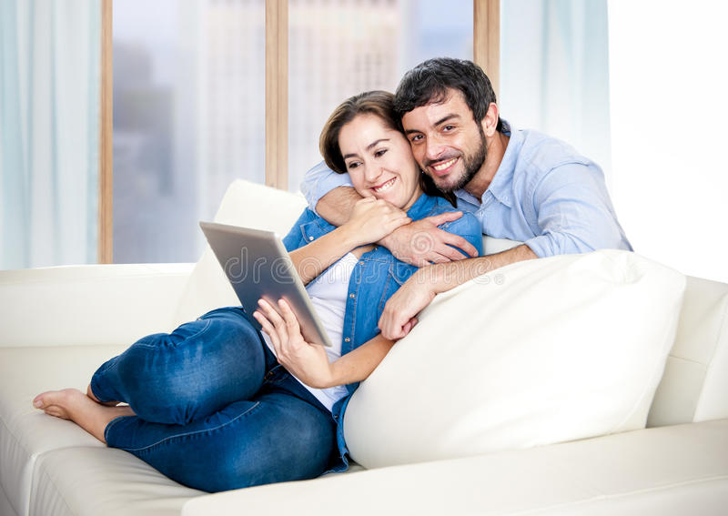 Pares latin bonitos no amor que encontra-se junto no sofá do sofá da sala de visitas que aprecia usando a tabuleta digital foto de stock