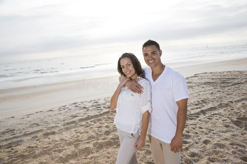 Pares latino-americanos afectuosos que estão na praia imagem de stock royalty free