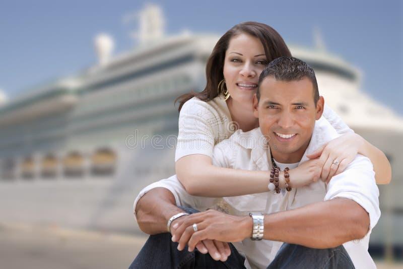 Pares latino-americanos felizes novos na frente do navio de cruzeiros imagem de stock