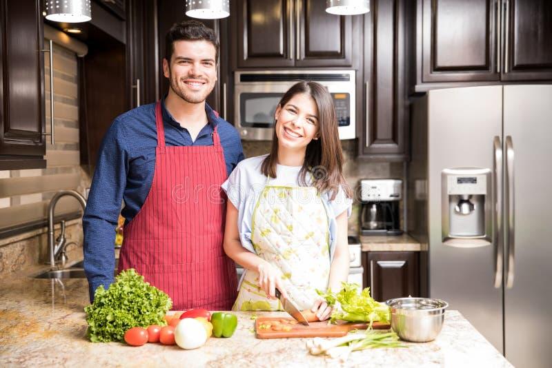 Pares latino-americanos que fazem a salada saudável na cozinha foto de stock royalty free