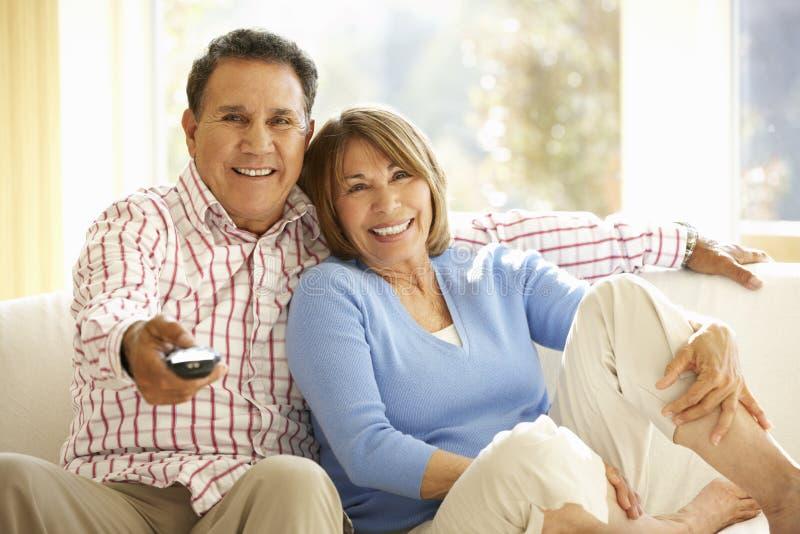 Pares latino-americanos superiores que olham a tevê em casa imagens de stock