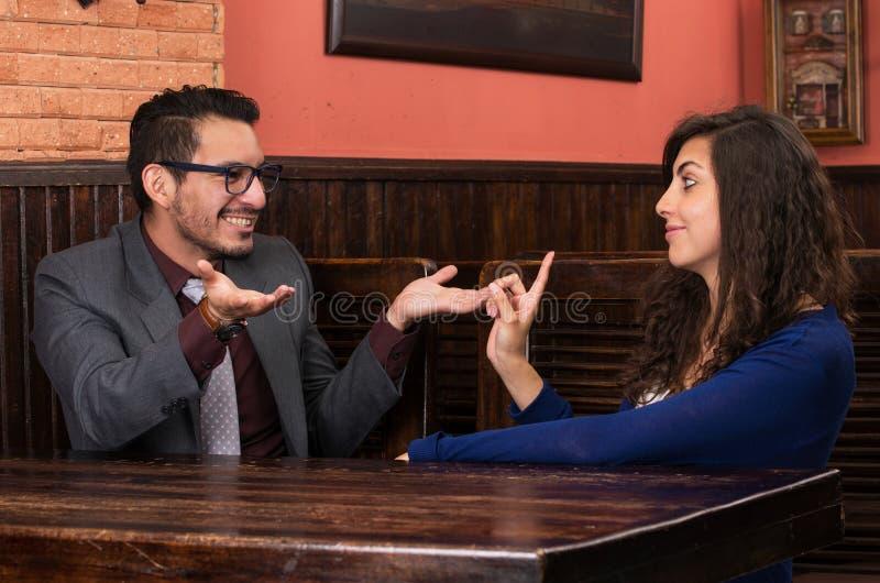 Pares latinos jovenes en un restaurante fotografía de archivo libre de regalías
