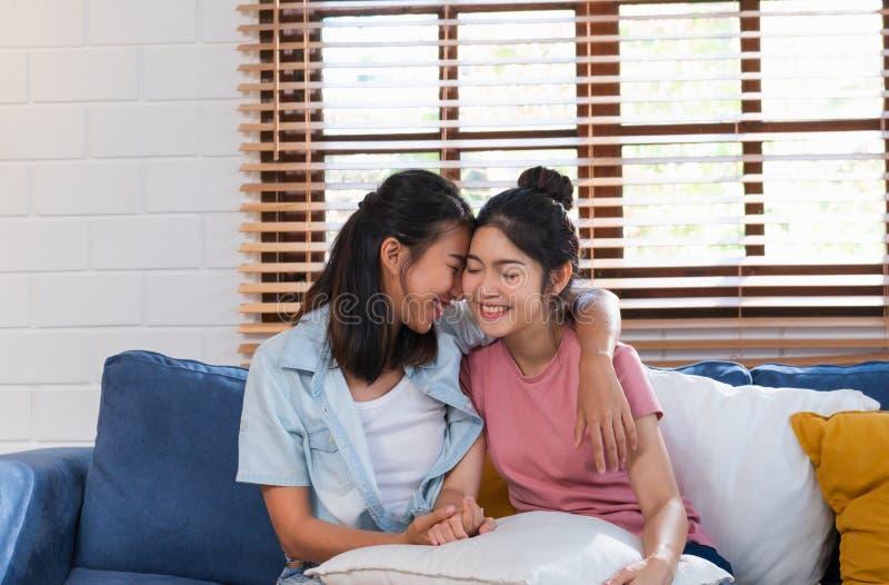 Pares lesbianos asiáticos felices abrazarse con amor en el sofá en la sala de estar en casa, concepto de la forma de vida de LGBT fotografía de archivo libre de regalías