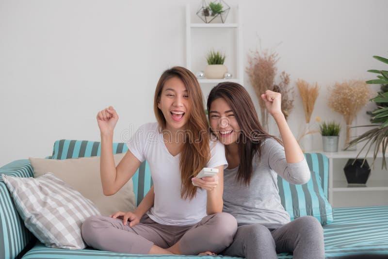 Pares lesbianos del lgbt de Asia que llevan a cabo la show televisivo y el che de observación del telecontrol imagen de archivo libre de regalías