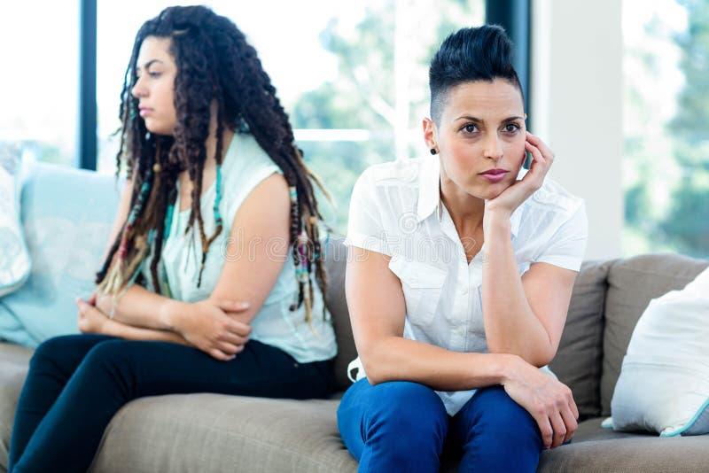Pares lesbianos infelices que se sientan en el sofá imagenes de archivo