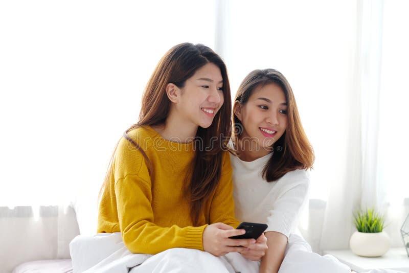 Pares lesbianos lindos jovenes de Asia usando el teléfono elegante con felicidad imágenes de archivo libres de regalías